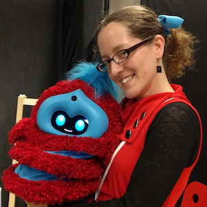 a woman in a red dress holding a red and blue striped robot and smiling