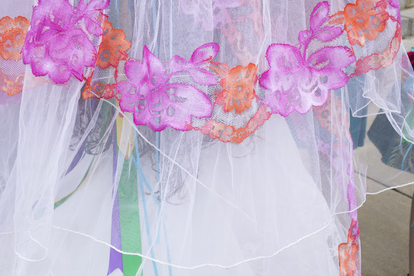 close up of lacy flowers on a veil, colored pink and orange