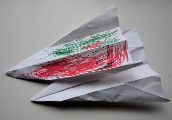 two paper airplanes, one has been colored on by a young child