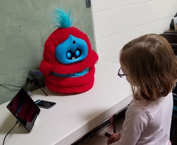 a child sits at a table that has a fluffy robot sitting on it