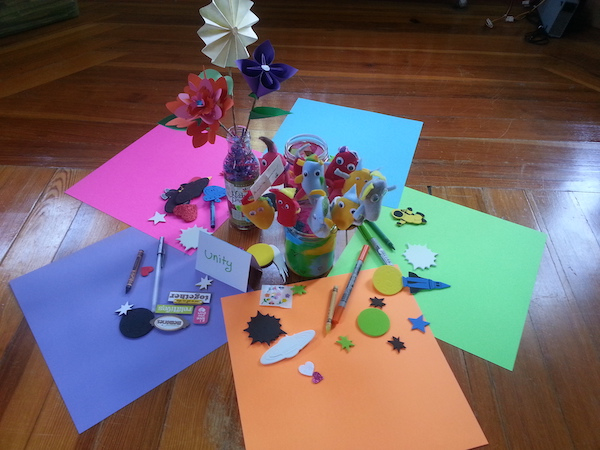 five colorful sheets of scrapbook paper arranged in a circle on the floor, with several jars in the middle containing a candle and paper flowers, with scrapbook materials scattered around