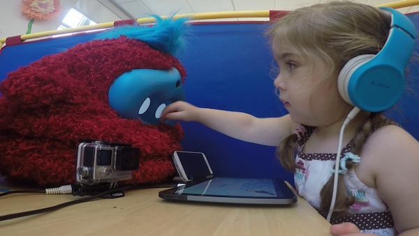 girl reaching across table to touch a fluffy robot's face