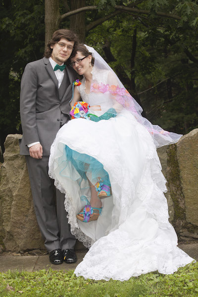 man in a tux and woman in a white wedding dress with colorful accents, in front of a stone wall at a park