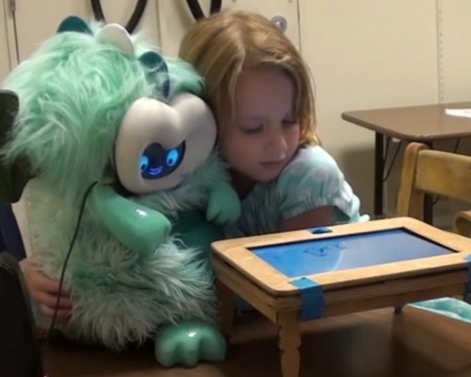 girl hugs fluffy dragon robot in front of a small play table