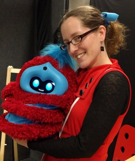 jacqueline holding the red and blue stripy fluffy tega robot, wearing a red dress