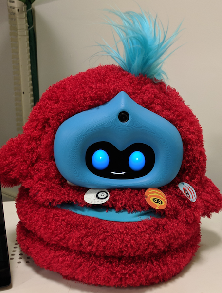 a fluffy red and blue tega robot with stickers stuck to its tummy
