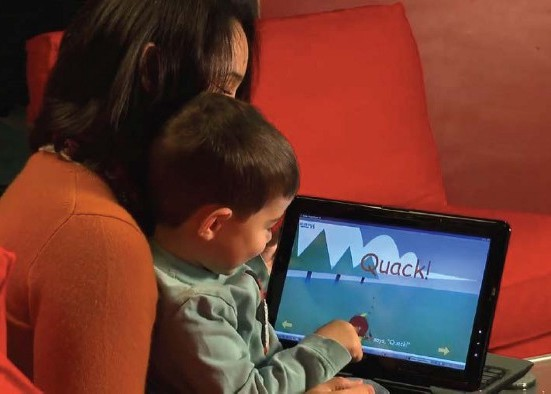 a mother sits with her son holding a tablet