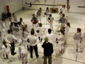 A group of fencers in white gear standing around.