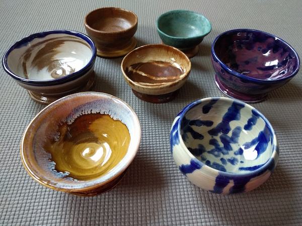 seven colorful bowls arranged in a circle with one in the middle, shown from the side so you can see that they are bowls
