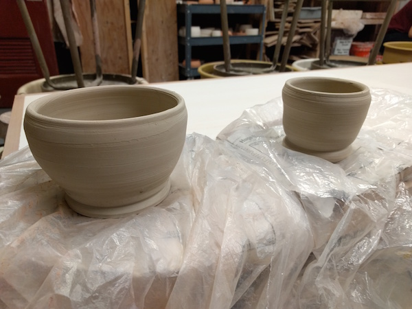 two white clay bowls, taller than they are wide, unglazed