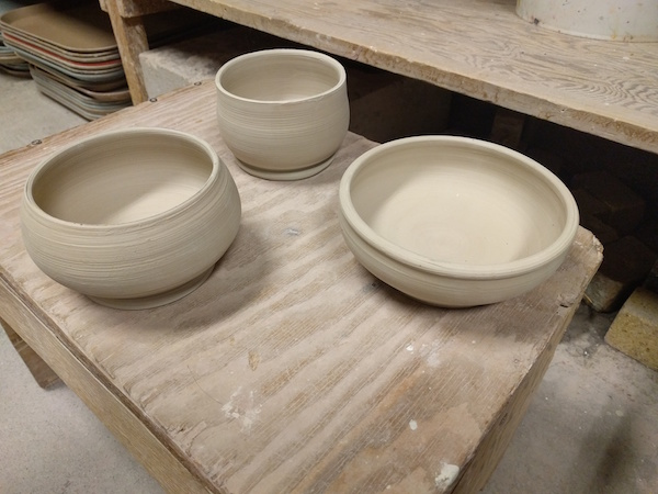 three white clay bowls sitting on a plank of wood