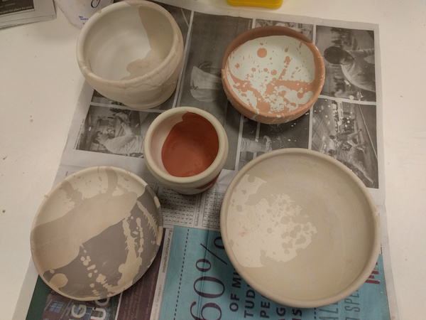 five glazed bowls before firing, in various dull shades of brown