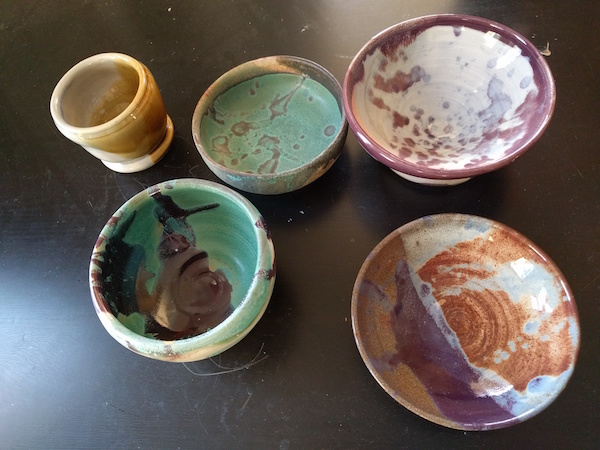 five glazed bowls after firing, shiny and brightly colored