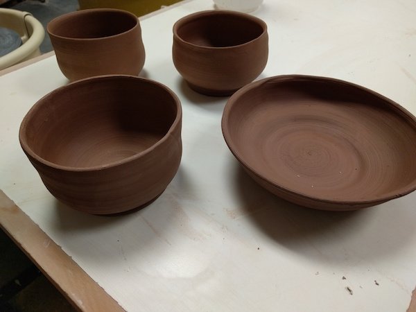 four brown clay bowls