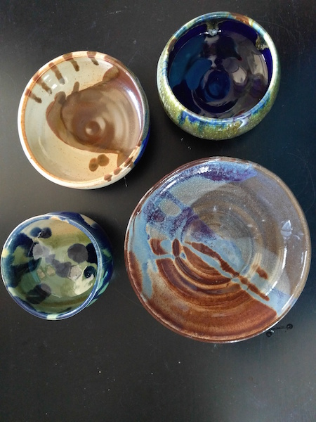four glazed, fired, colorful shiny bowls