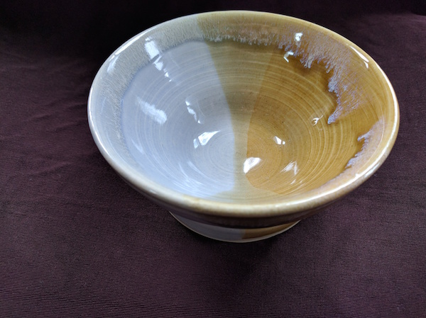 bowl half pale blue and half yellow-gold, with an hourglass-esque pattern where the colors overlap