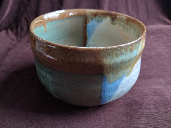 side view of a bowl with a rounded base and straight sides, glazed half sea green and half white, with brown along the rim
