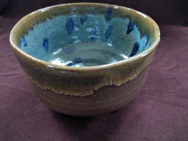 side-top view of a brown bowl with turquoise and blue polka dots inside