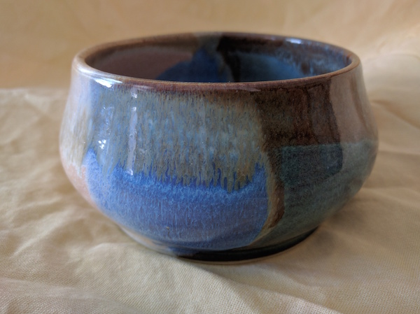 side view of a bowl with a round bulging base, fairly straight sides and a thin rim, glazed in browns and blues