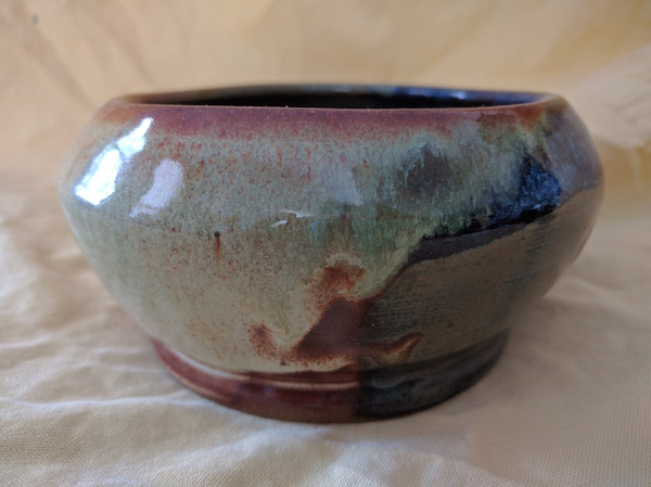 side view of a bowl that is narrow at the bottom, bulges out, and is somewhat narrower at the top, glazed in sea green, rusty brown, and blue