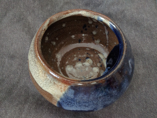 bowl with an opening smaller at the top, brown and blue glazes with white spots