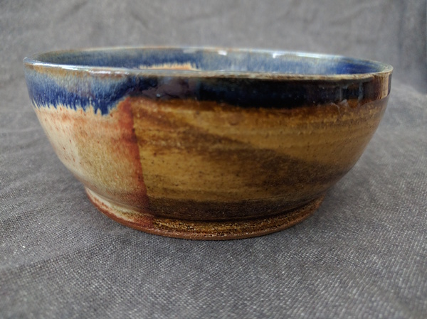 side view of a round marbled clay bowl, yellow-gold with a blue rim
