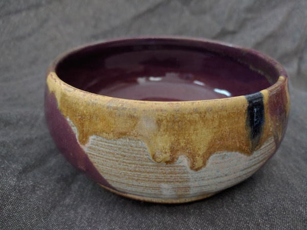 side view of a round, flat bowl, purple inside, white and yellow-gold matte outside