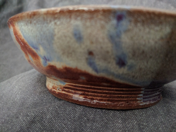 side view of the base of a bowl that has five small ridges circling the bottom before the bowl flares up and out
