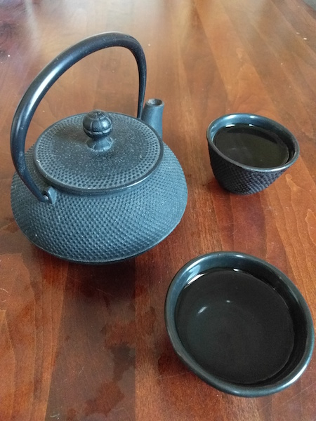 metal teapot on a table next to two matching round teacups