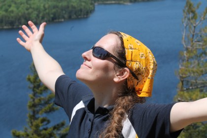 Jacqueline M. Kory-Westlund wearing sunglasses on a mountain, arms outstretched with a happy smile