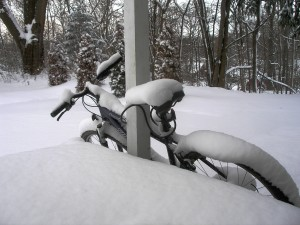 bicycle leaned against a porch, layers of snow on the handlebars, seat, and tires