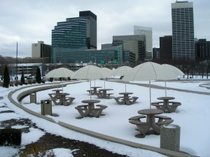 a flock of round picnic tables, cream-colored umbrellas shading benches of snow, with the buildings of Cleveland rising in the background