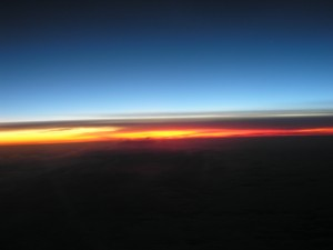 curve of the earth with dark blue above and glowing yellow-red on the horizon