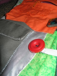 close up of a red button by a green pocket and an orange pocket