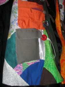 a zippered orange pocket above a flapped grey-green pocket on the side of the patchwork coat