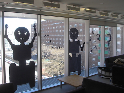 paper robots hung on windows saying 'am I alive?'