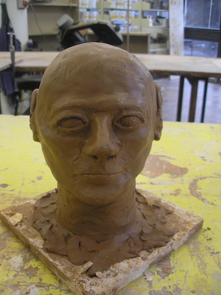 a bald head sculpted in brown clay, features a little rough around the edges