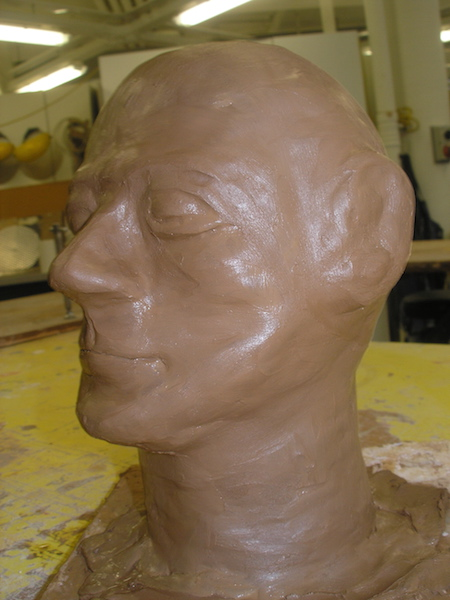 a bald clay head, features smoothed and shiny