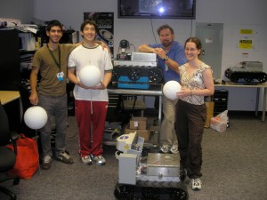 four people standing around a pair of boxy robots