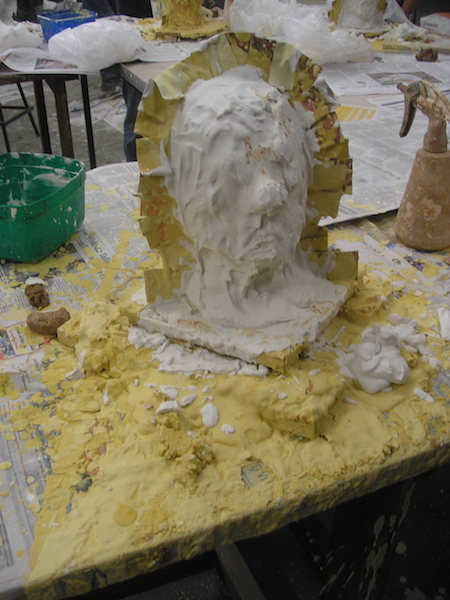 head with metal shim fence, looking blob-like with the last thick coat of plaster applied