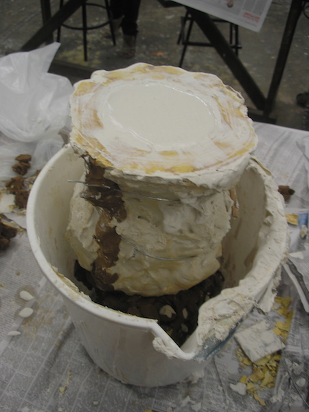 mold tied together, upside-down in a bucket, wet plaster visible in the opening at the neck