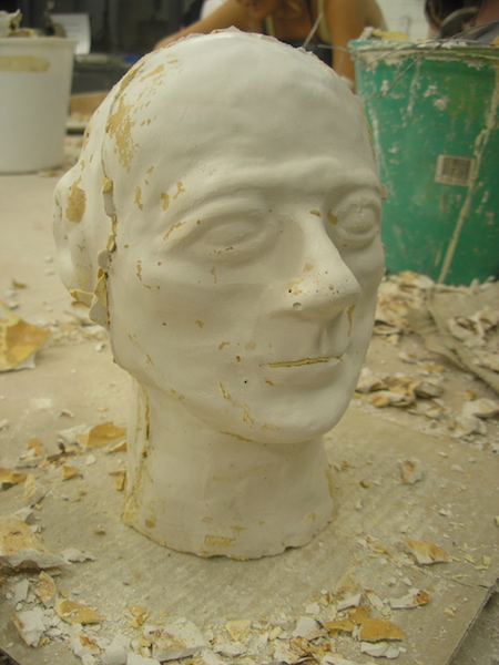 plaster head with rough patches, excess plaster from the mold stuck in the ears, mouth, and seam line