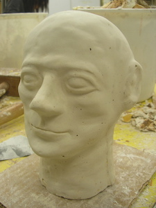 a plaster casting of a human head, smoothed, with calm, rounded features and a slight smile