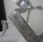 Two strips of steel bent into the outline of a puzzle piece and have been spot welded in place where they overlap