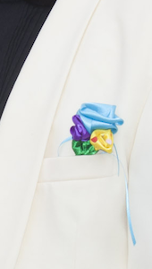 ribbon flower boutonniere attached with a pin to a suit jacket pocket