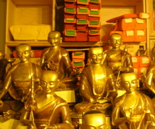 _several gold shiny buddha statues stacked in front of a set of box shelves_