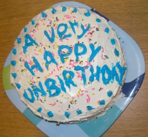 "_white-frosted round cake with blue icing proclaiming ""a very happy unbirthday!""_"