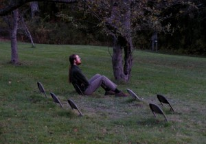 _man sitting on one of a series of folding chairs that are half-buried in the grass_