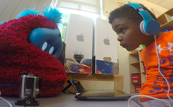 a boy sits at a table with a fluffy robot on it and leans in to peer at the robot's face, while the robot looks down at a tablet