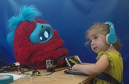 a girl mimics the head tilt and expression shown by a fluffy robot